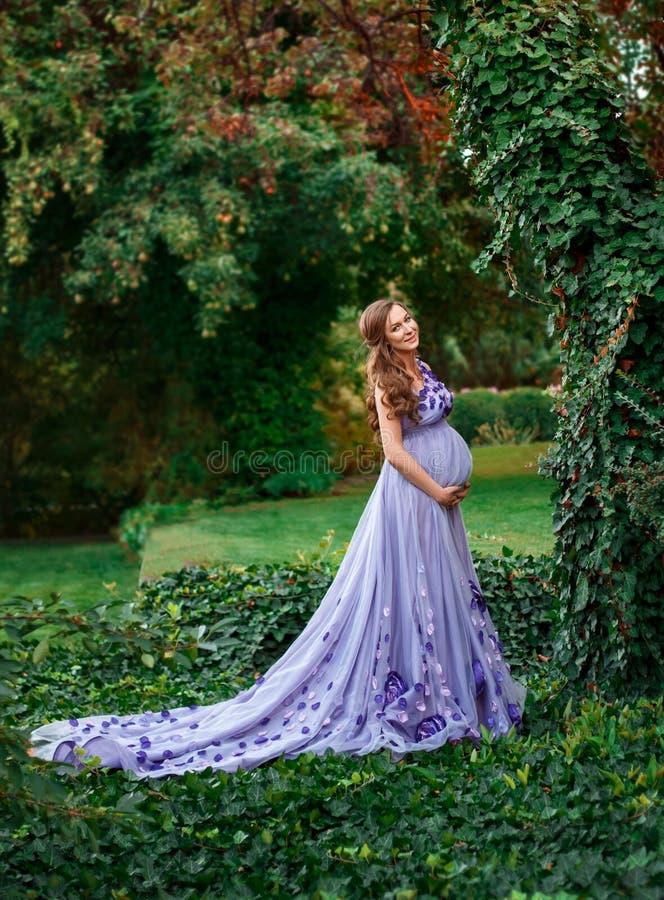 Ett elegant, gravid kvinna går i en härlig trädgård i en lyxig blom- lila klär med ett långt drev kronärtskockan arkivbilder
