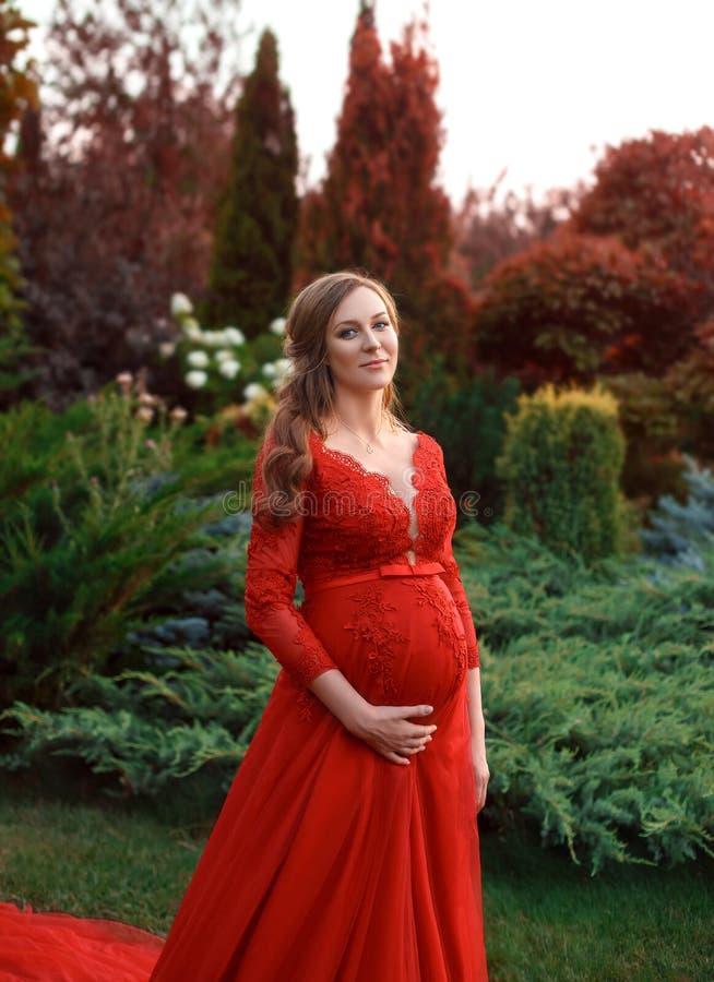 Ett elegant, gravid kvinna går i en härlig trädgård i en lyxig dyr röd klänning med ett långt drev kronärtskockan royaltyfri foto
