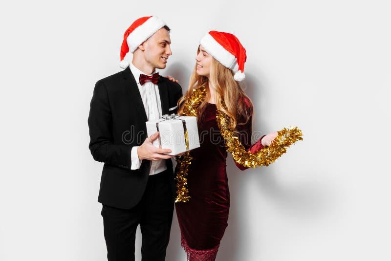Ett elegant par av vänner i Santa Claus hattar som firar Nen royaltyfria foton