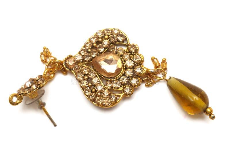 Ett enkelt stycke av konstgjort fejkar det guld- örhänget för kopplingen tillbaka arkivfoton