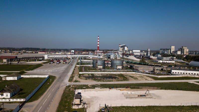 Ett enormt oljeraffinaderi med metallstrukturer, r?r och destillation av komplexet med brinnande ljus p? skymning flyg- sikt arkivbild