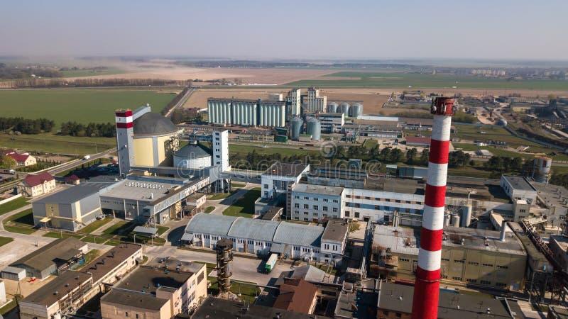 Ett enormt oljeraffinaderi med metallstrukturer, r?r och destillation av komplexet med brinnande ljus p? skymning flyg- sikt royaltyfri foto