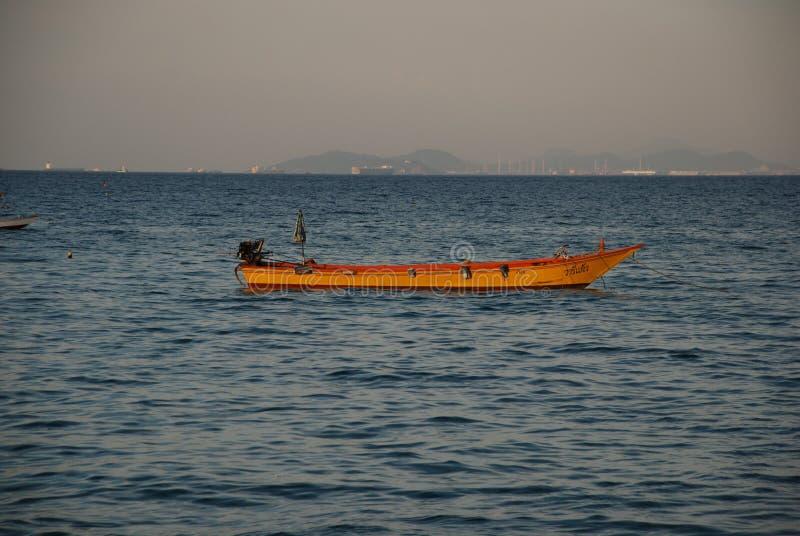 Ett ensamt fartyg i ljuset av inställningssolen i porten av Pattaya arkivfoton