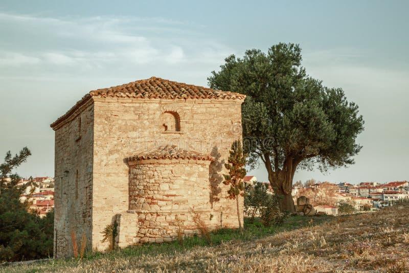 Ett ensamt forntida kapell under ett träd på kullen av havscoasna arkivbild