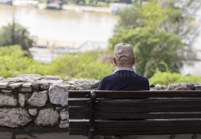 Ett ensamt gamal mansammanträde på en bänk i en parkera som ser floden royaltyfri fotografi