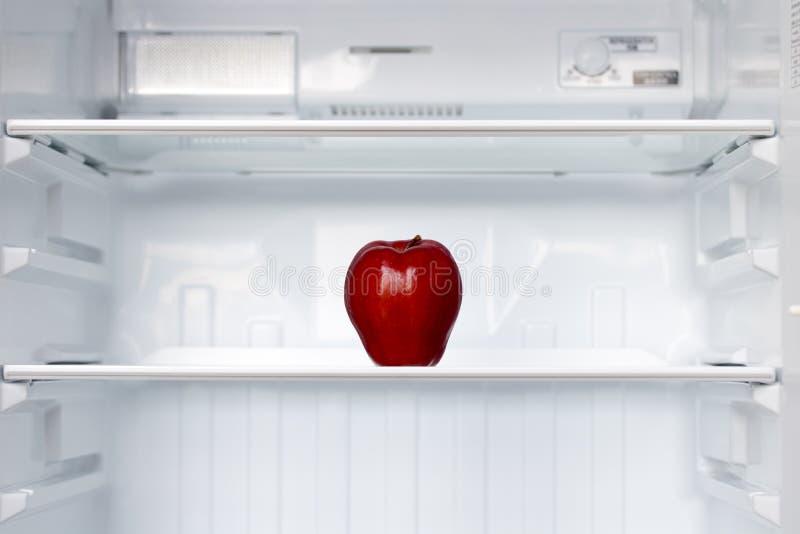 Ett ensamt rött äpple på en hylla i en tom kyl royaltyfria foton