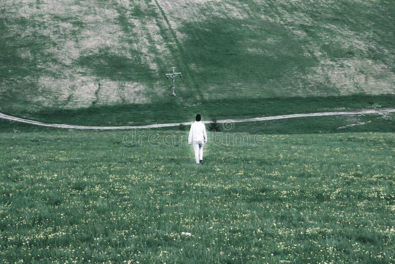 Ett ensamt vitt glödande diagram av en man går till och med en dyster gr arkivfoton