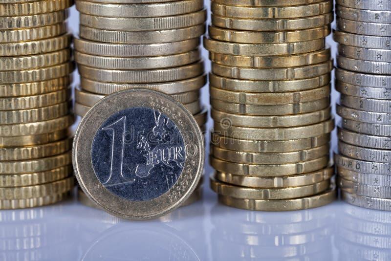 Ett ett euro mynt framme av många mer mynt som staplas i kolonnnolla arkivbilder