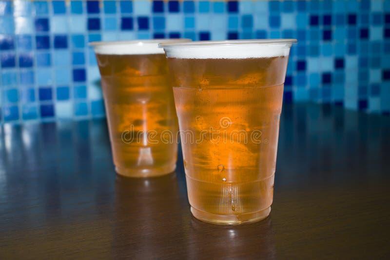 Ett exponeringsglas av öl är på tabellen royaltyfri bild