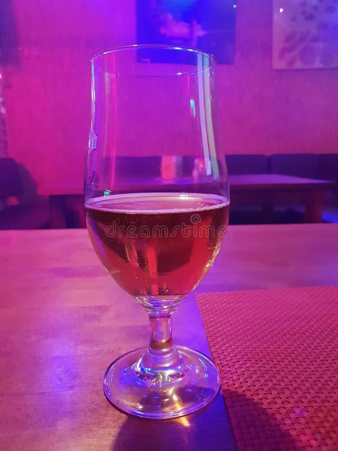 Ett exponeringsglas av öl i restaurangen med olika diskoljus från att dansa golvet under partiet i stången, restaurang, nattklubb royaltyfri foto