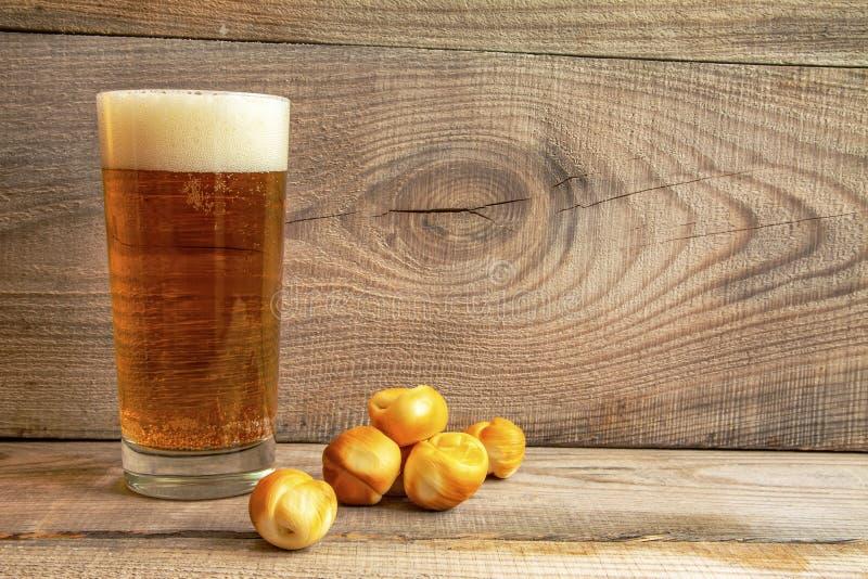 Ett exponeringsglas av öl med ost klumpa ihop sig på en träbakgrund royaltyfri bild