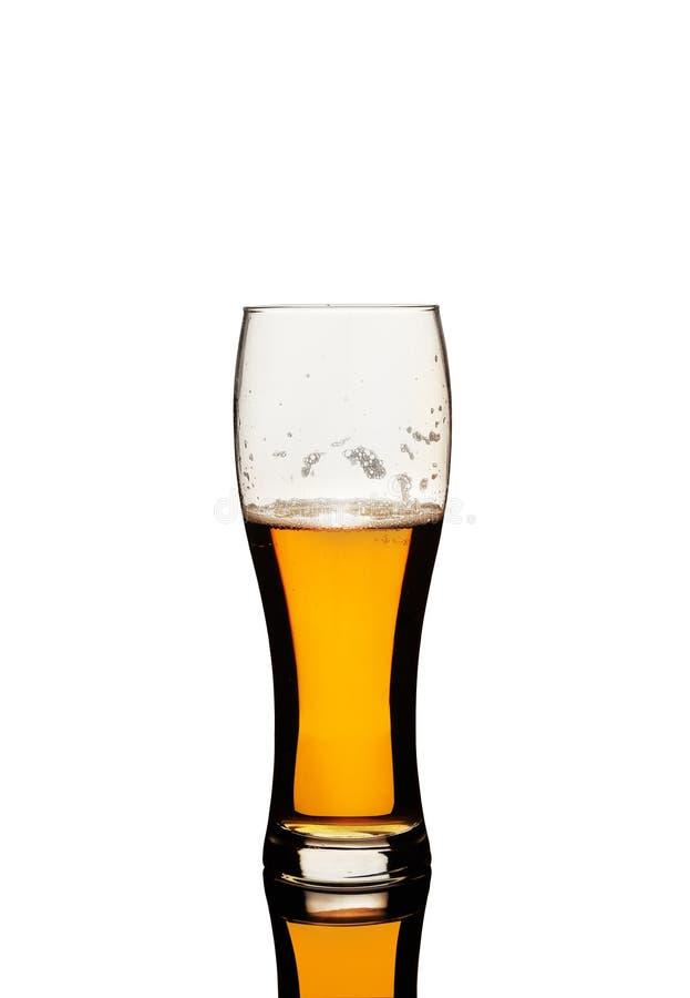 Ett exponeringsglas av öl på en vit bakgrund royaltyfri foto