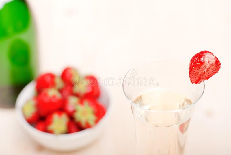 Ett exponeringsglas av champagne med jordgubbar, närbild royaltyfria bilder