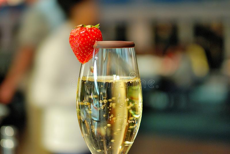 Ett exponeringsglas av champagne med jordgubben royaltyfri foto