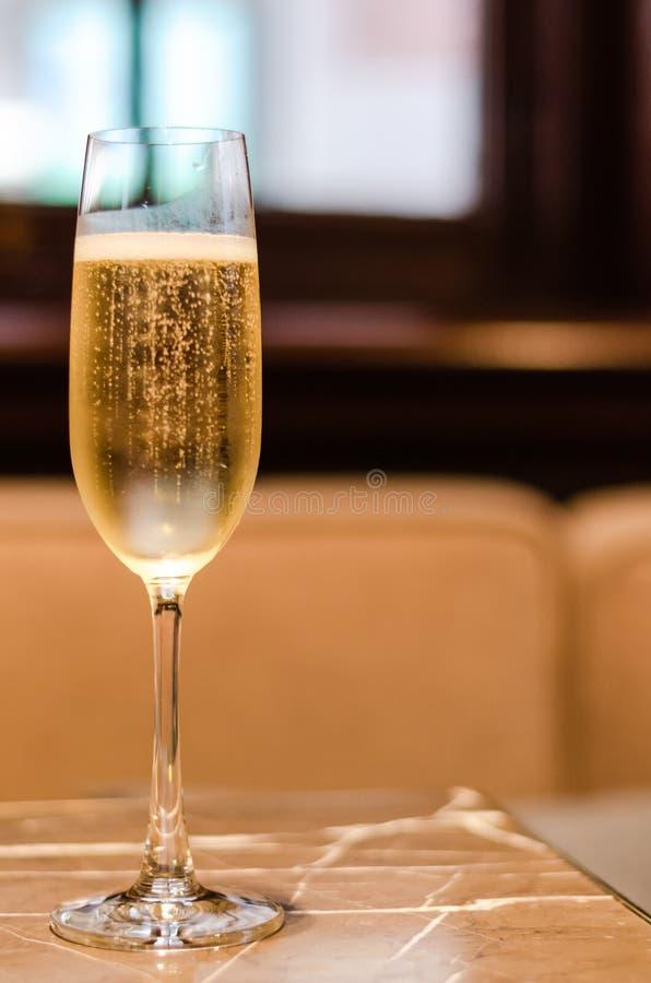 Ett exponeringsglas av Champagne sätter på marmortabellen i restaurangen för beröm med suddig bakgrund arkivbild