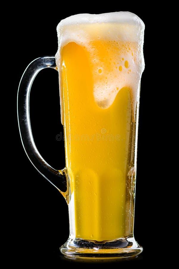 Ett exponeringsglas av frostigt nytt ljust ofiltrerat öl med skum på mörker arkivfoto