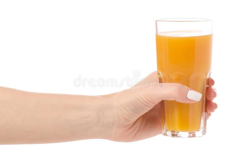 Ett exponeringsglas av fruktsaft i handen av en orange persikamango royaltyfria foton