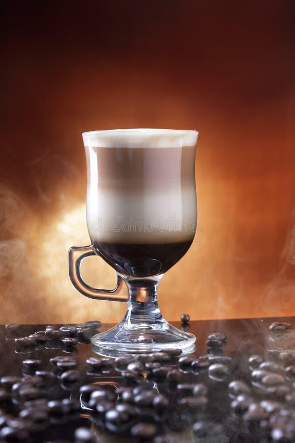 Ett exponeringsglas av kaffelatte på en tabell som strilas med kaffebönor Latte är en kaffedrink som göras med espresso, och ånga arkivbilder