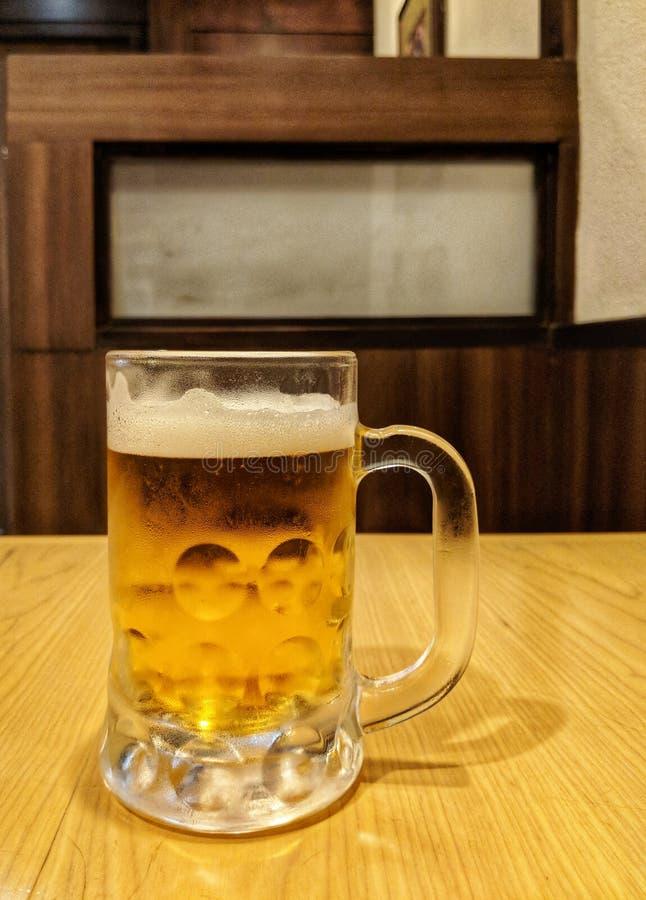 Ett exponeringsglas av kallt nytt öl på en trätabell royaltyfria bilder