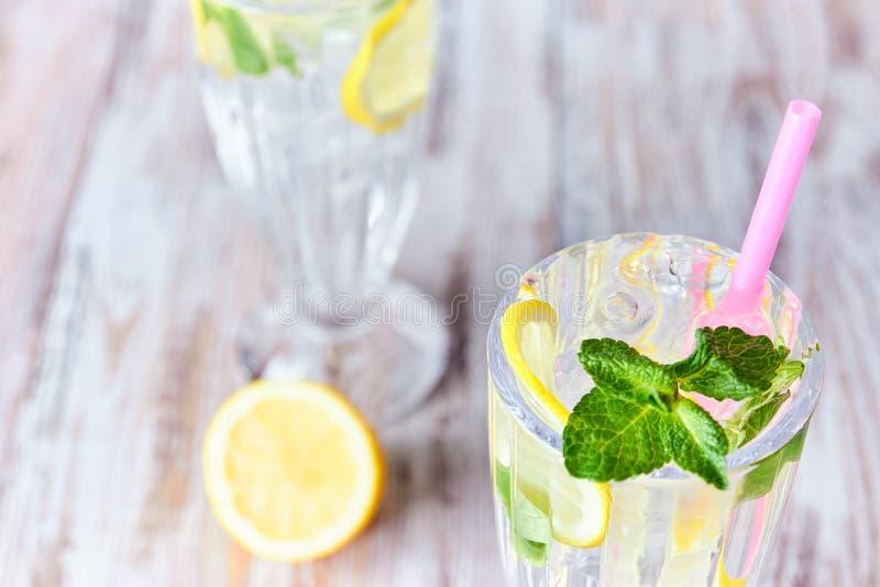 Ett exponeringsglas av kallt vatten med is, citronen och mintkaramellen Selektivt fokusera Uppfriskande sommardrink close upp Kop arkivbilder