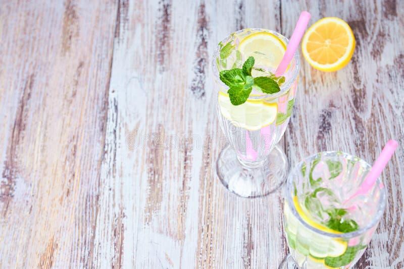 Ett exponeringsglas av kallt vatten med is, citronen och mintkaramellen Selektivt fokusera Uppfriskande sommardrink close upp Kop arkivfoton