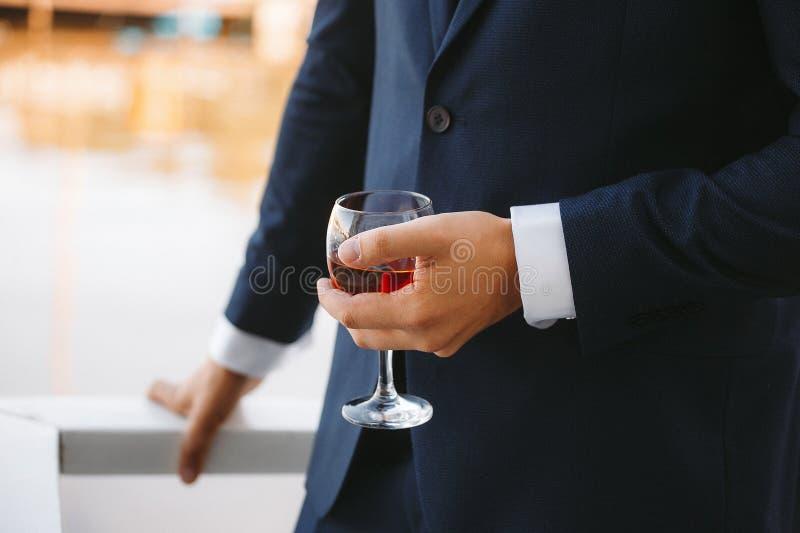 Ett exponeringsglas av konjak i händerna av brudgummen royaltyfri fotografi