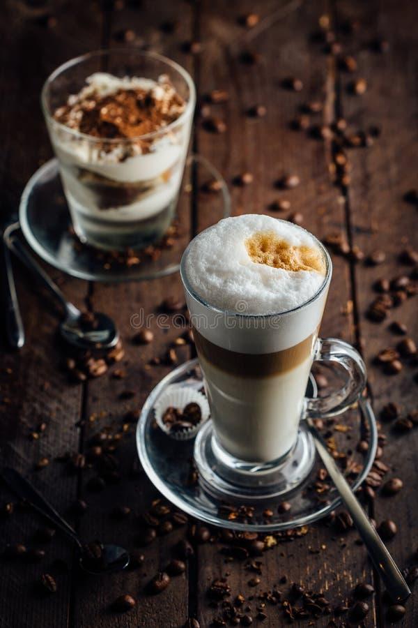 Ett exponeringsglas av kryddig latte med piskad kräm och kanel som står på ett brunt bräde bönor frukosterar ideal isolerad makro arkivbild
