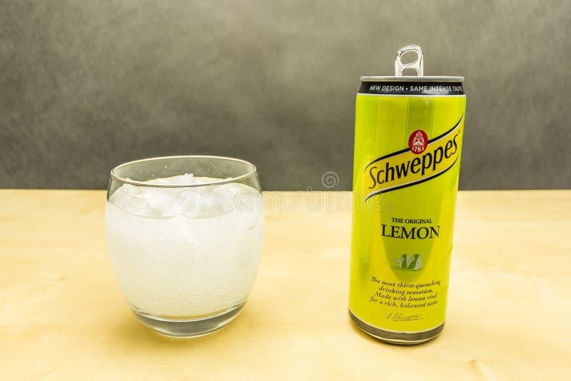 Ett exponeringsglas av lemonad med citronanstrykning och iskuber från Schweppes royaltyfri fotografi