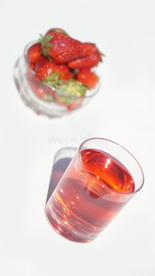 Ett exponeringsglas av ljus röd hallon-jordgubbe den söta kalla drinken med en kopp av jordgubbar i bakgrunden royaltyfria bilder