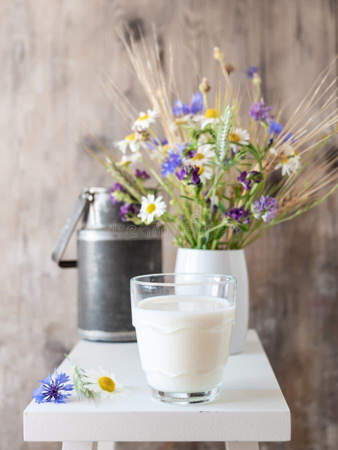 Ett exponeringsglas av mjölkar i en lantlig stil med vildblommor royaltyfria foton