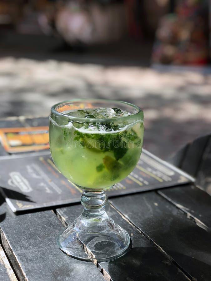 Ett exponeringsglas av mojito på en tabell i en mexicansk stång Mojito i det original- exponeringsglaset är bredvid menyn royaltyfri bild