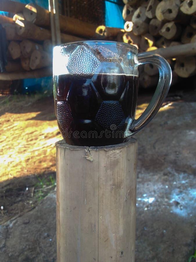 Ett exponeringsglas av morgonkaffe på en bambu för arbete arkivfoto