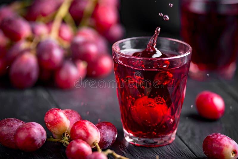 Ett exponeringsglas av ny druvafruktsaft, druva Juice Canning Mörka bakgrund, färgstänk och droppar i ett exponeringsglas fotografering för bildbyråer