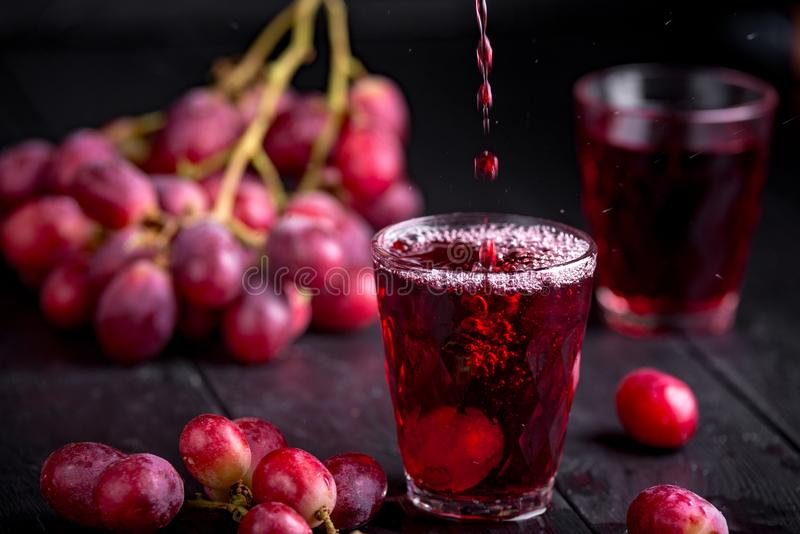 Ett exponeringsglas av ny druvafruktsaft, druva Juice Canning Mörka bakgrund, färgstänk och droppar i ett exponeringsglas royaltyfri bild