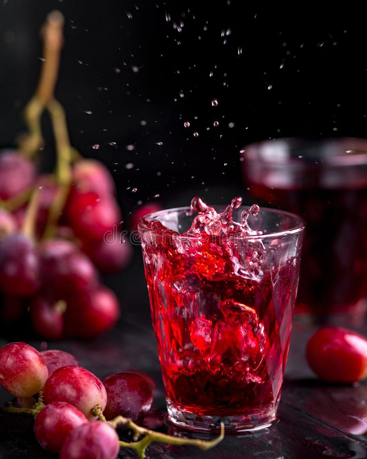 Ett exponeringsglas av ny druvafruktsaft, druva Juice Canning Mörka bakgrund, färgstänk och droppar i ett exponeringsglas royaltyfria bilder