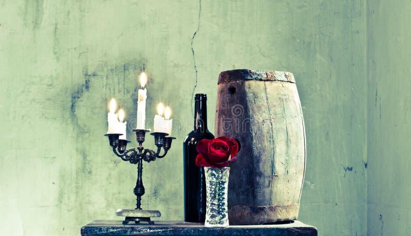 Ett exponeringsglas av nytt vin i källaren med en trumma och en röd ros som ska önskas arkivfoton