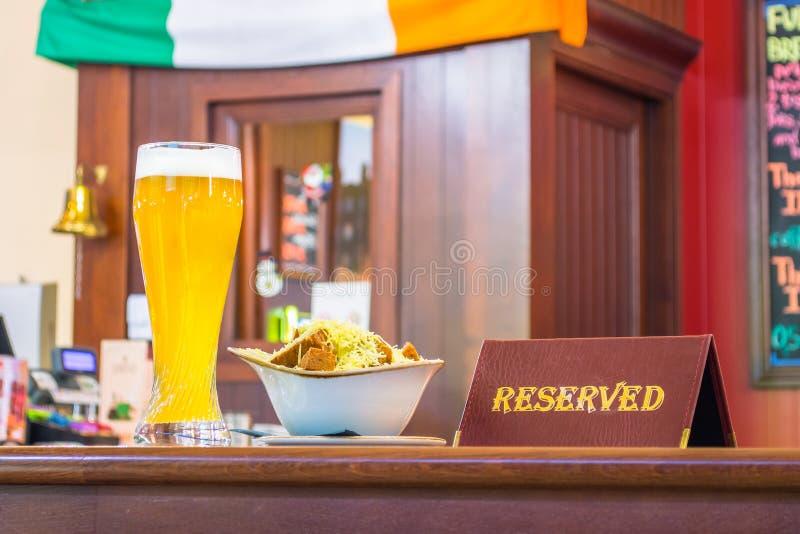 Ett exponeringsglas av ofiltrerat öl med skorpaost, en minnestavla - reserveras på en trätabell i restaurangstången arkivbilder