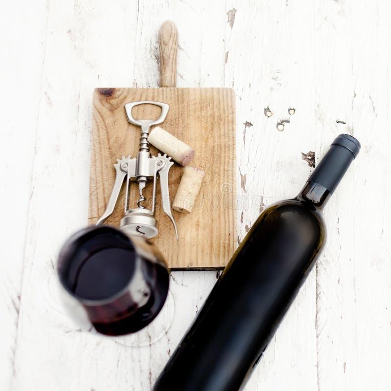 Ett exponeringsglas av rött vin-, flask-, korkskruv- och vinkorkar på rusti royaltyfri bild