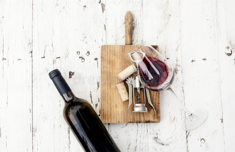 Ett exponeringsglas av rött vin-, flask-, korkskruv- och vinkorkar på rusti royaltyfri fotografi