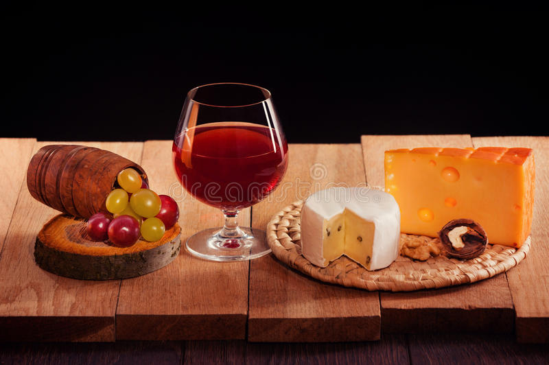 Ett exponeringsglas av rött vin med ost, druvor och muttrar royaltyfri fotografi