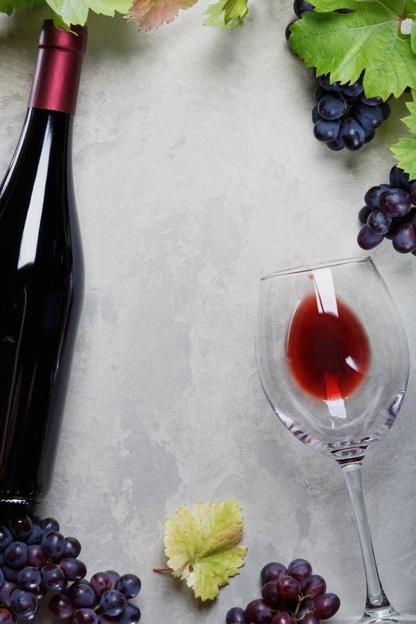 Ett exponeringsglas av rött vin och en flaska av druvor och druvasidor på tabellen royaltyfri bild