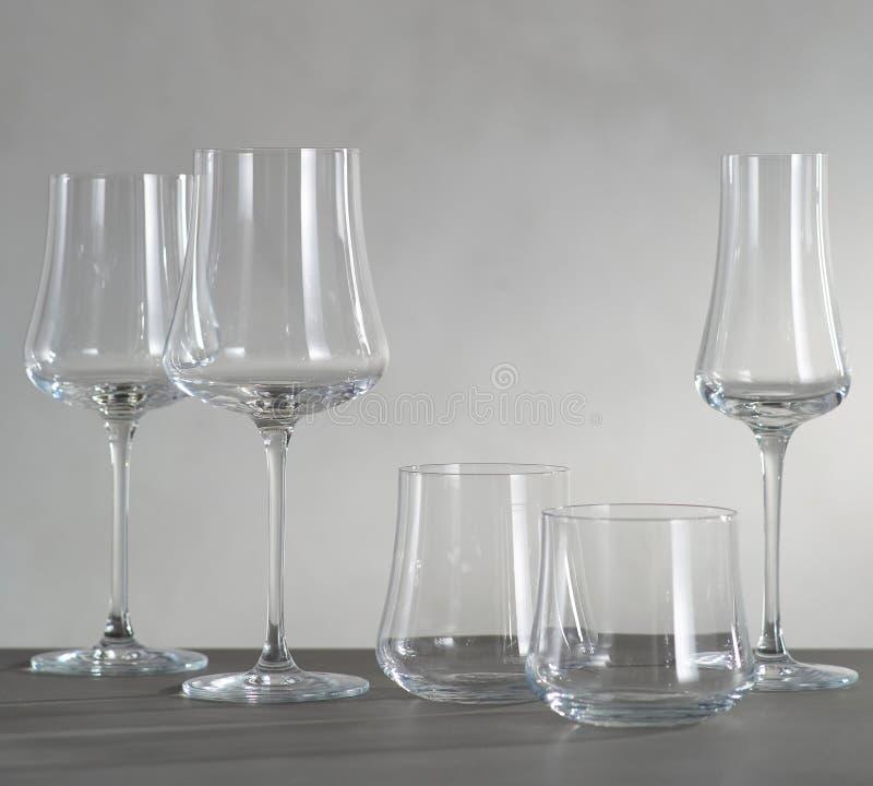 Ett exponeringsglas av rött vin och fyra tomma vinexponeringsglas arkivfoto