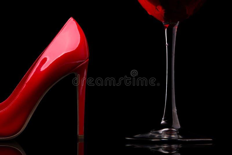 Ett exponeringsglas av rött vin- och kvinnors skor med häl royaltyfria bilder