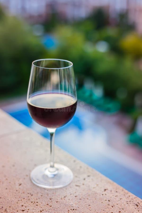 Ett exponeringsglas av rött vin på balkongen, simbassängbakgrund arkivbilder