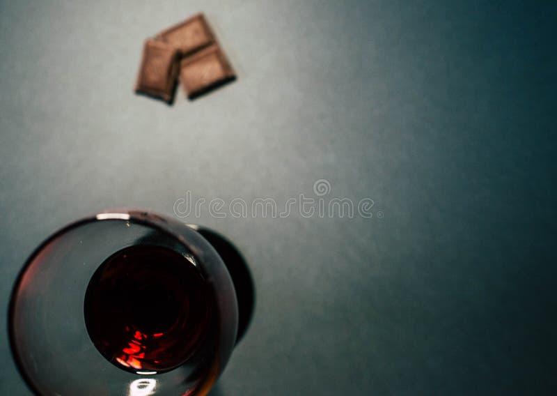 Ett exponeringsglas av r?tt vin med chokladskivor arkivfoton