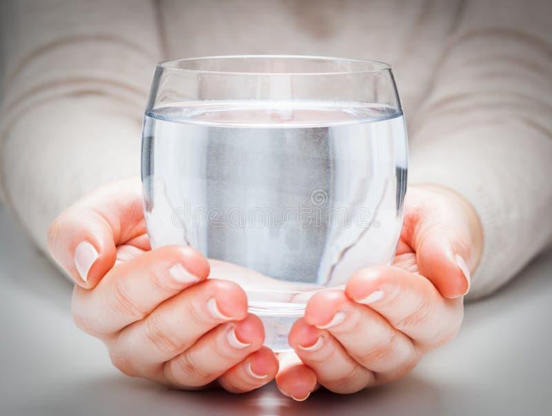 Ett exponeringsglas av ren mineralvatten i kvinnas händer Miljöskydd, sund drink royaltyfria bilder