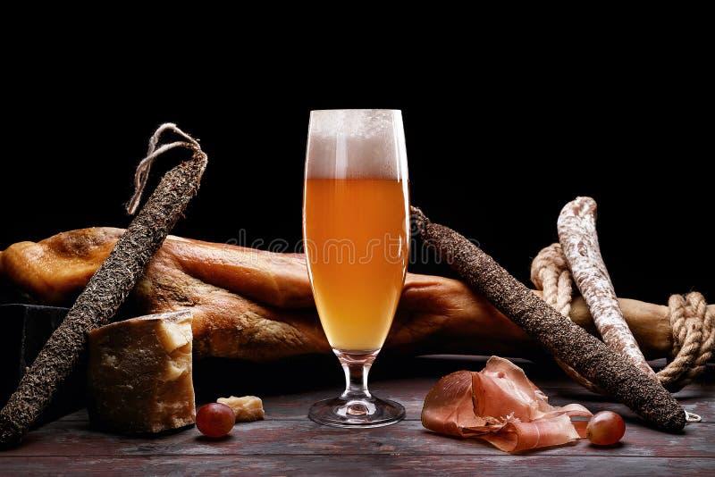 Ett exponeringsglas av skum för ljust öl, ben, Parma skinka, dyra variationer av korven och ost med formen royaltyfria bilder