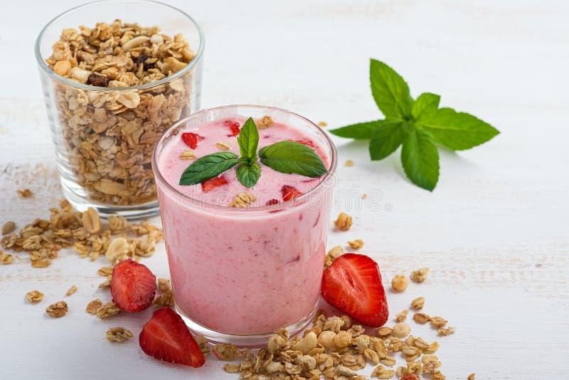 Ett exponeringsglas av sund jordgubbeyoghurt med den nya bär, mysli och mintkaramellen på en vit trätabell sund frukost arkivbild