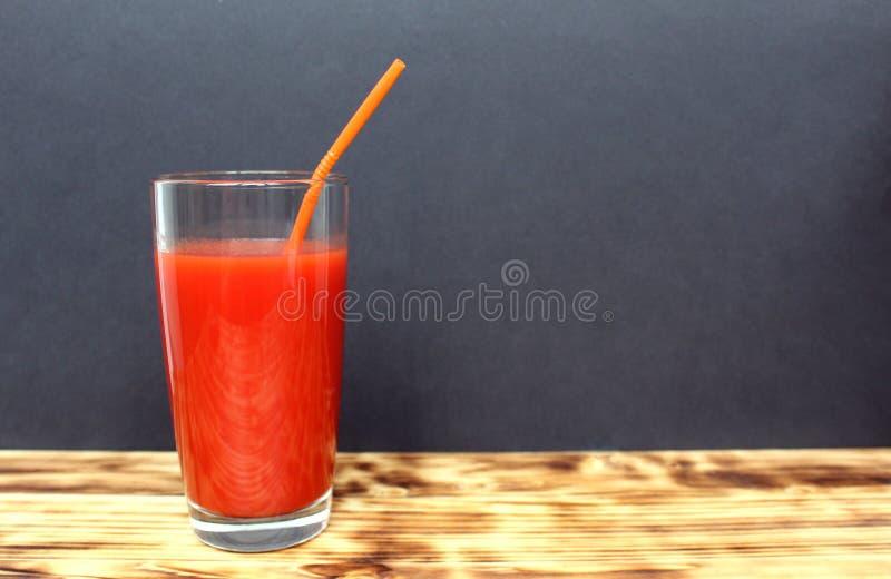 Ett exponeringsglas av tomatfruktsaft med tomater och ett rör arkivfoton