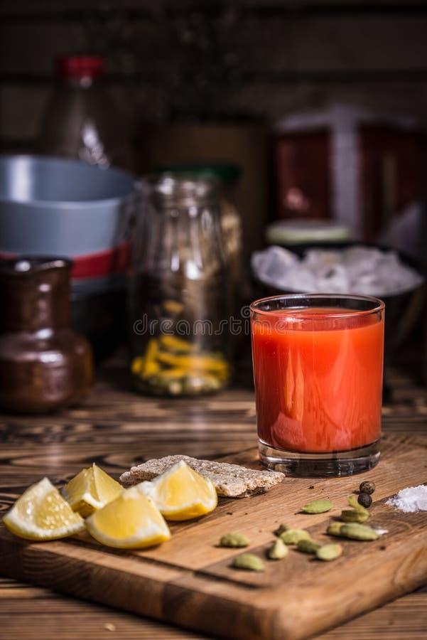 Ett exponeringsglas av tomatfruktsaft på ett träbräde med citronskivor, saltar och pumpafrö arkivfoton